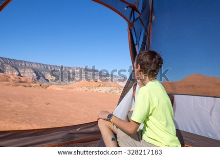 Child  sits at the entrance to the tent and looking at the beautiful wild landscape of rocky desert. Grand Staircase-Escalante National Monument, Utah - stock photo