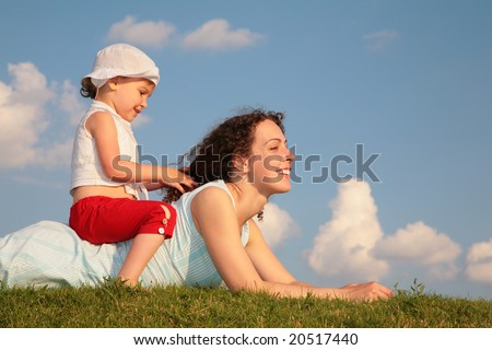 Child sits on back of mother lying on grass - stock photo