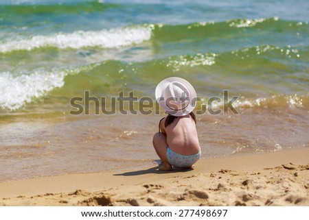 Child sits with his back to the camera on the shore of a tropical beach, watching the waves. Selective focus on the baby. Space for text. - stock photo
