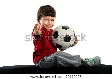 child sits with soccer ball and shows the finger at the camera, isolated on white background - stock photo