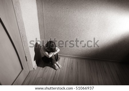 Child sitting in a room corner - stock photo