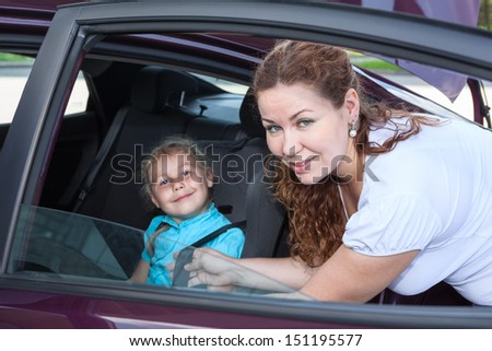 Child sitting in baby car seat and mother helping - stock photo