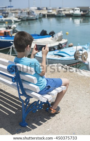 Child sitting on a bench on the beach in front of boats.  - stock photo