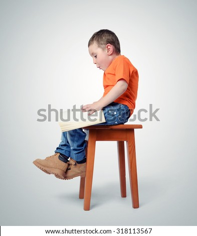 Child sitting on a chair with a book - stock photo