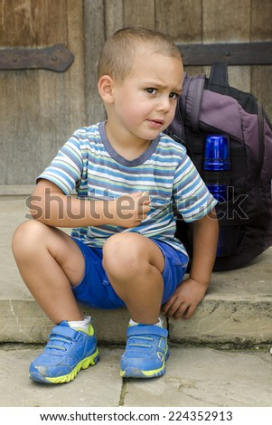 Child sitting on a step outside, snacking and resting during a walk trip or trek.  - stock photo