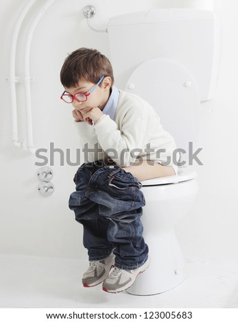Child sitting on a toilet - stock photo