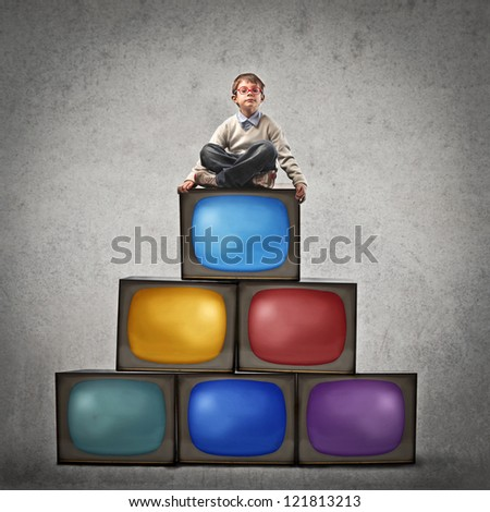 Child sitting on many televisions - stock photo