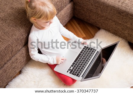 Child sitting on the ground with laptop in her lap  - stock photo