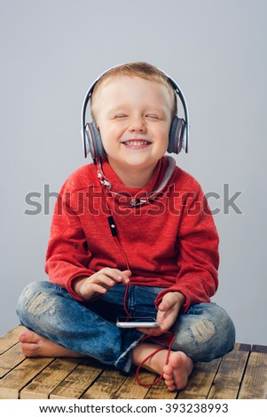 Child sitting with crossed legs and listening to music. Boy with headphones holding smartphone and closing his eyes while listening to music - stock photo