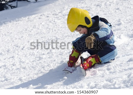 Child skier sitting on snow after falling down whilst learning skiing.  - stock photo