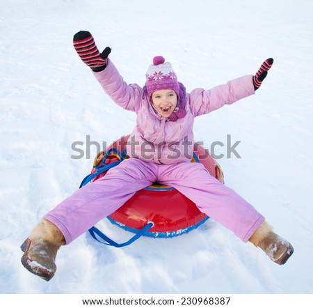Child sledding in winter hill. Happy girl tobogganing - stock photo