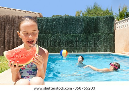 Child smiling eating a slice of watermelon by a swimming pool with group of joyful children having fun playing in a home garden on a sunny holiday, outdoors. Active kids lifestyle exterior vacation. - stock photo