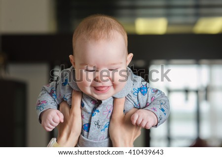 Child smiling mother. Mom raised her child above head. Happy charming 5-month-old baby girl smiling and grimacing in female hands. Home interior in background.  Mother throws up baby, playing indoors. - stock photo