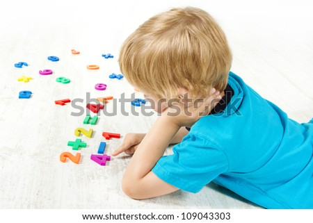Child solve the mathematics example. Looking for answer. - stock photo