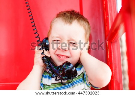 child speaks on the phone in noisy environments. kid hand closed his ears and squeezed his eyes shut while talking on the phone in red telephone box. noisy surroundings, problem with phone connection - stock photo