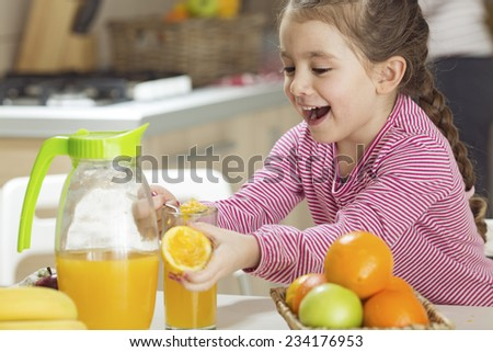 Child squeezing juice  - stock photo