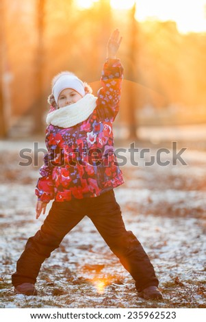 Child standing in the rays of the setting sun with a raised hand, winter - stock photo
