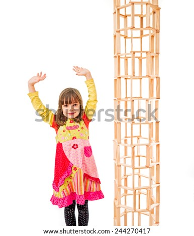 Child standing next to a tower out of blocks - stock photo