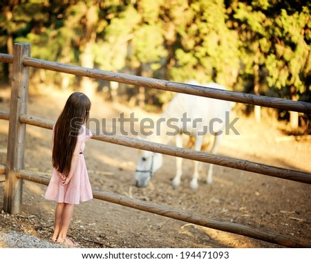 Child standing standing in front of corral and watching white horse eating - stock photo