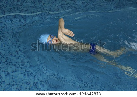 Child swimmer in swimming pool. Blue color swimming pool - stock photo