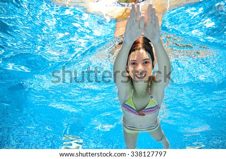 Child swims in pool underwater, happy active girl has fun in water, kid sport on family vacation  - stock photo