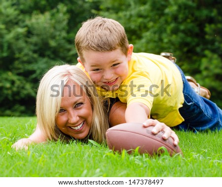 Child tackling mom while playing football together outdoors - stock photo