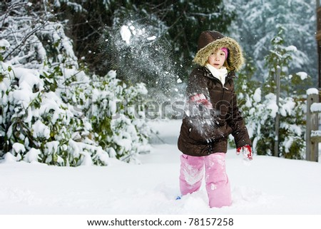 child throwing a snowball - stock photo