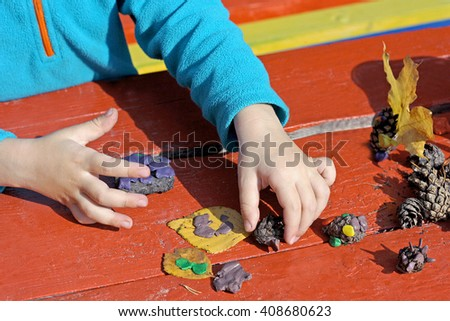 Child to play outdoors. The image is part of small child playing with plasticine in the street behind a red wood Desk. A child plays with clay and various natural materials with different shapes. - stock photo