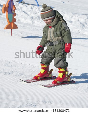 Child toddler learning to ski in winter skiing resort. - stock photo