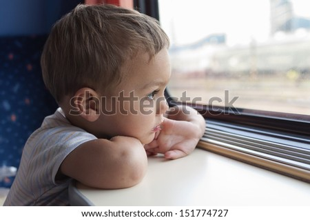 Child traveling on train looking through the window. - stock photo