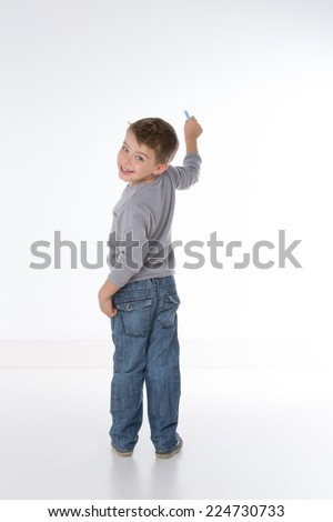 child turns back while writing on a wall - stock photo