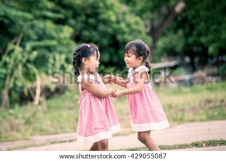 Child two girls having fun to play together in the park,vintage color filter - stock photo