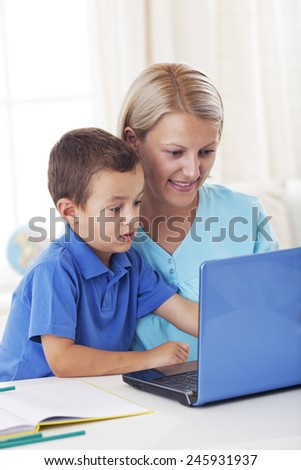 Child using laptop with his mother - stock photo
