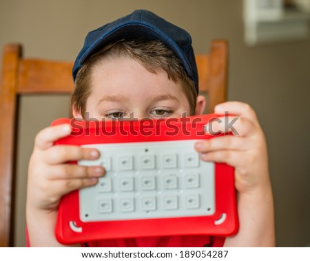 Child using tablet computer while sitting at dining room table - stock photo