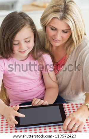 Child using tablet pc with mother at kitchen table - stock photo