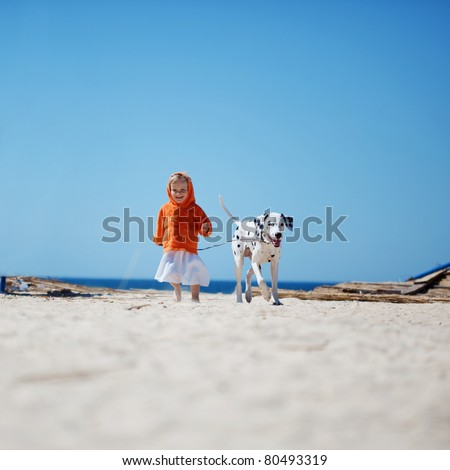 Child walking alone with her lovely dog at beach - stock photo