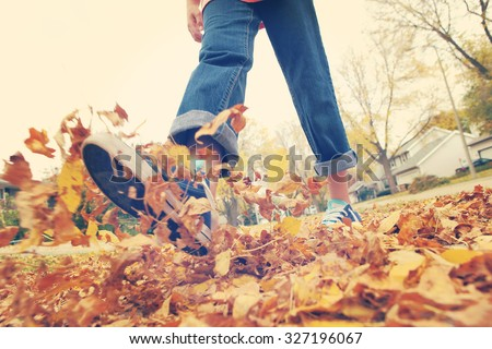 Child walking and kicking fall leaves. Focus on leaves in center.  Motion blur on legs, Instagram filtered effect. - stock photo