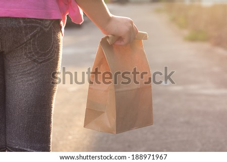 Child walking to school, with paper lunch bag - stock photo