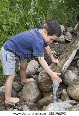 Child washing hands in water stream with wooden fountain.  - stock photo