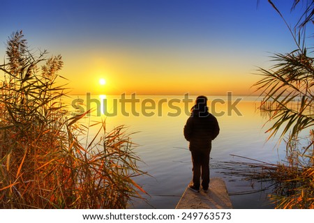 child watching the sunrise - stock photo