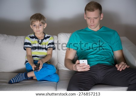 Child watching tv and dad using phone in the house - stock photo