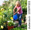 Child watered from watering the flowers in the garden - stock photo