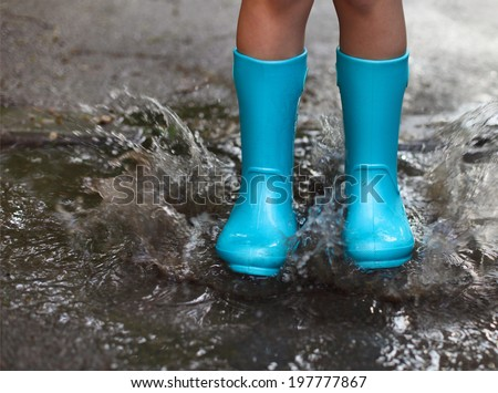 Child wearing blue rain boots jumping into a puddle. Close up - stock photo