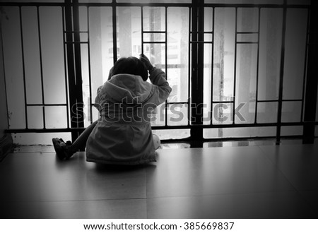Child who has trapped is look like a very sad sit and looking light far from window. - stock photo