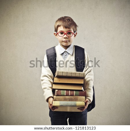 Child with a backpack holding some books - stock photo