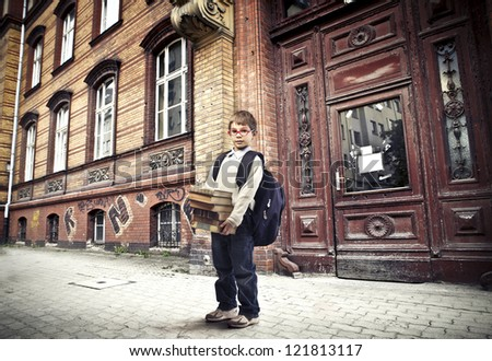 Child with a backpack holding some books near a school - stock photo
