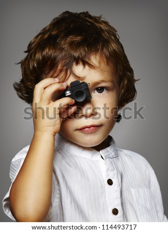 child with a small camera on grey background - stock photo