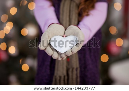 Child with a white Christmas heart displayed in cupped gloved hands surrounded by a bokeh of twinkling festive lights on a Christmas tree - stock photo