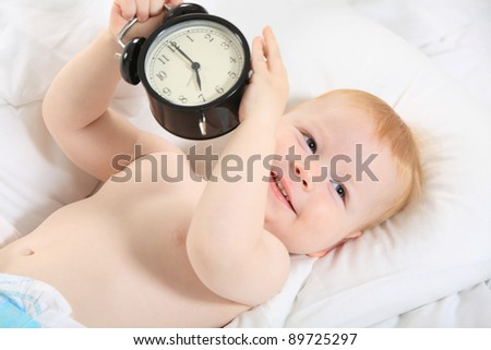 child with an alarm clock lying on the bed, and wishes everyone a good morning - stock photo