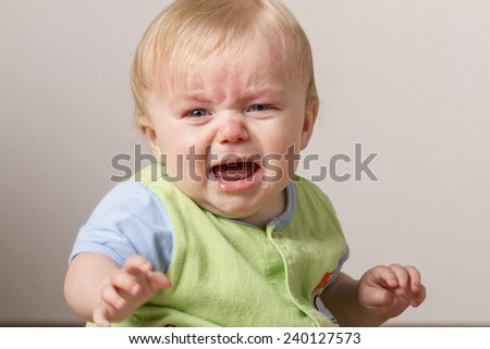 Child with arm stretched out while crying at something - stock photo